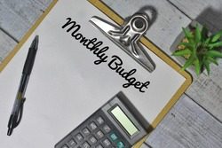 Top view of calculator, pen and paper clipboard with text Monthly Budget