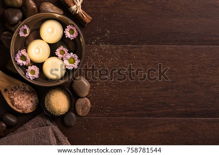 Top view of candles with salt and pebbles on wooden background with copy space. Burning candle in water with flowers, rock salt and towels at luxury spa. High angle view of aromatherapy set at salon. #758781544