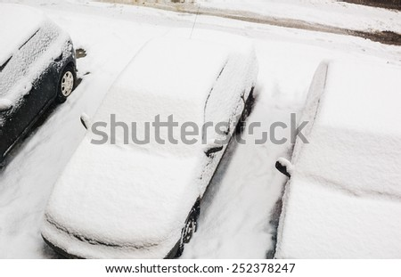 top view of car cover after snowfall. On a snow - no noise. This is a snow surface. Focus on a windshield of center car.