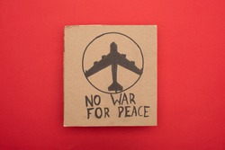 top view of cardboard placard with no war fro peace lettering and airplane on red background