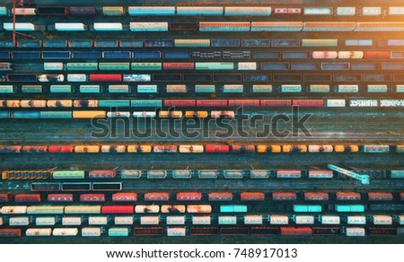 Top view of cargo trains. Aerial view from flying drone of colorful freight trains on the railway station. Wagons with goods on railroad. Heavy industry. Industrial conceptual scene with trains.