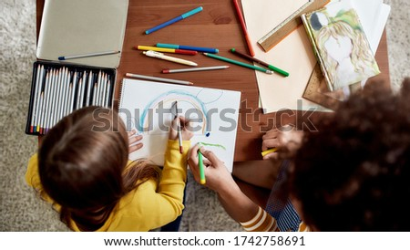 Top view of caucasian little girl spending time with african american baby sitter. They are drawing a mouse together. Children education, leisure activities, babysitting concept. Selective focus Foto stock ©