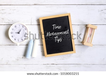 Top view of chalk,table clock,hourglass and blackboard written with 'TIME MANAGEMENT TIPS' on white wooden background.