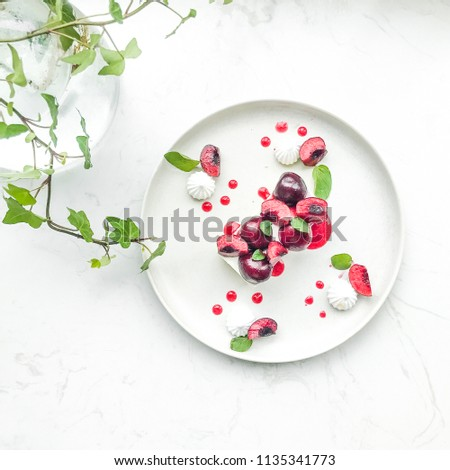 Top view of Cherry slice, cherry cake with mint on white marble table in minimal cafe decorate with small plant. (foody on social media concept)