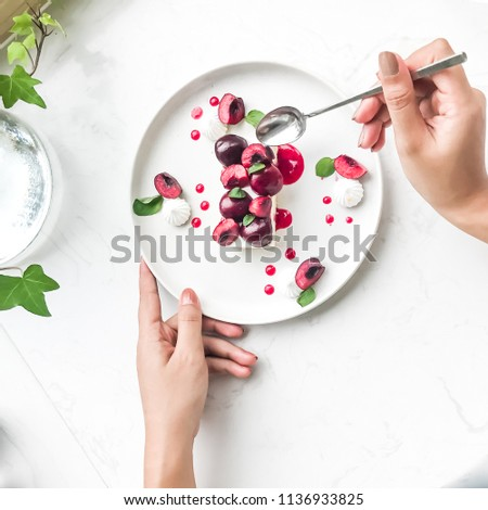 Top view of Cherry slice, cherry cake with mint on white marble table in minimal cafe decorate with small plant. (hand in frame on social media concept)
