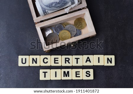 Top view of chest box, money banknote, coins and scrabble letters with text UNCERTAIN TIMES over black background.  Stock photo ©
