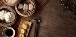 Top view of Chinese steamed dumpling and steamed pork bun in a bamboo steamer with chopstick on wooden table with copy space