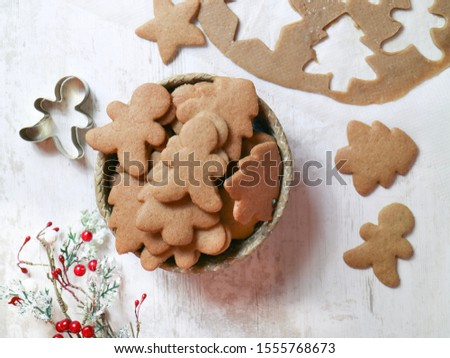 Top view of Christmas cookies with mold and uncooked part of flour after cut on a wooden table