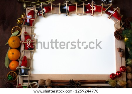 Top view of Christmas decor with copy space area. Christmas objects: dried sliced orange, mandarines, cinnamon, pine cone, fir branch, cup coffee, cheesecake, walnut, golden Christmas bells