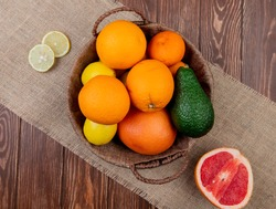 top view of citrus fruits as orange avocado lemon in basket with grapefruit on sackcloth and wooden background