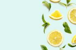 Top view of citrus slices and mint herbs frame on retro mint pastel background with copyspace. Minimal fruit concept design.