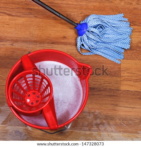 top view of cleaning of wooden floors and red bucket with washing water