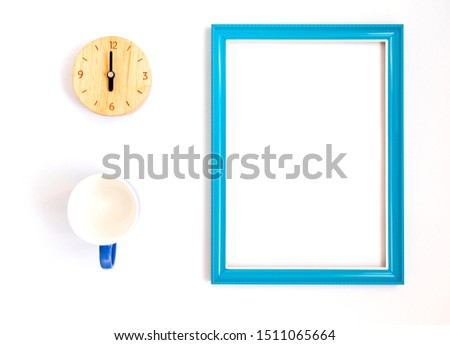 Top view of clock made wooden and a cup. There are blue picture frame with inside empty space . Placed on white background.