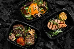 Top view of coal cooked healthy food in take away boxes for delivery