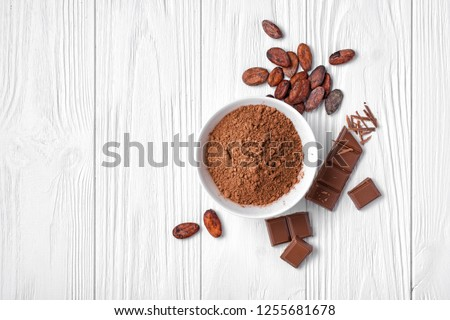 Top view of cocoa powder with broken chocolate bar and cocoa beans for confectionery on white wooden background with copy space