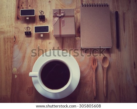 Top view of coffee and stationery mock up set with coffee, paper clip, small black board, notebook and pen in retro filter effect