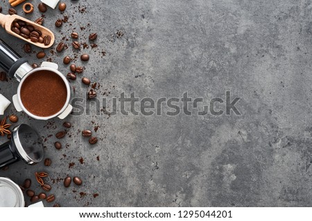 Top view of coffee background. Assorted coffee beans, ground coffee, portafilter and tamper on dark concrete background. Flat lay. Copy space for text. Barista concept.