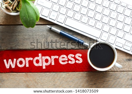 top view of coffee cup and keyboard with wordpress inscription on table