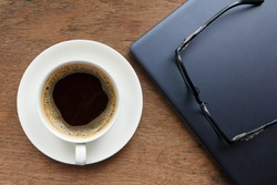 Top view of coffee cup , glasses and laptop on wooden table