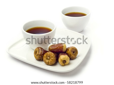 Top view of coffee cups with dates in a plate. - stock photo