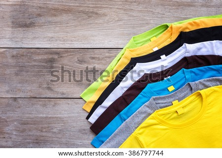 Top view of color T-Shirt on grey wood plank background #386797744