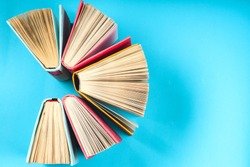 Top view of colorful hardback books in a circle and magnifying glass. free copy space. Back to school copy space. Education background.