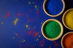 top view of colorful traditional holi powder in bowls isolated on dark background.Space for text . happy holi.Concept Indian color festival called Holi