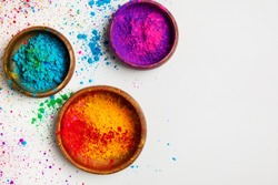 top view of colorful traditional holi powder in bowls isolated on white