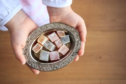 Top view of colorful Turkish delight in silver bowl on the little girl hands. Traditional ramadan holiday in Turkey. Turkish culture concept.