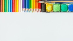 Top view of Colorful Watercolor palette, paintbrush, colored pencils and drawing equipment on white background and copy space