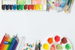 Top view of Colorful Watercolor palette, paintbrush, colored pencils, ruler and drawing equipment on white background and copy space