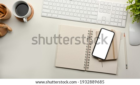Top view of computer desk with keyboard, smartphone, stationery and coffee cup, clipping path