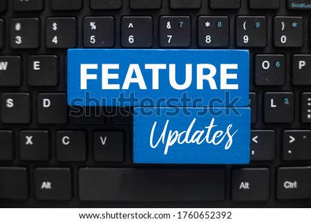 Top view of computer keyboard and blue wooden cube written with Feature Updates. Foto stock ©