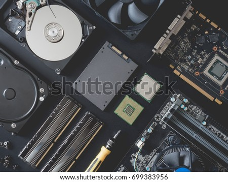 top view of computer parts with harddisk, ram, CPU, graphics card, solid state drive (SSD), motherboard, tools on black steel background.