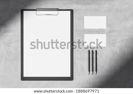 Top view of concrete desktop with blank clipboard, business cards and three pens. Mock up, 3D Rendering Foto stock ©