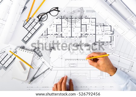 Top View of Construction plans and Male Hands drawing on blueprints; Architectural and Engineering Housing Concept.