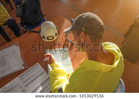 Top view of construction worker setting on the chair writing Job Safety Hazard control risk assessment (JHA) working at height permit prior commence work of each task construction site