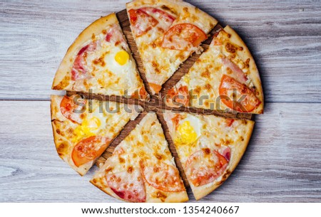 Top view of cooked pizza cutted in six portions over the wooden background. Delicious pizza on the table. View from above.