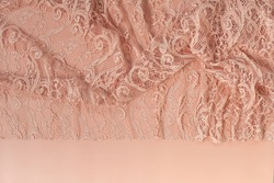 Top view of coral coloured lace fabric with patterns on light peach coloured background. Closeup of beautiful and delicate coral lace fabric detail from a ladies evening gown. Wedding dress detail.