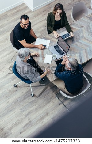 Top view of corporate business team sitting around a table and discussing. High angle view of business people having a brainstorming session.