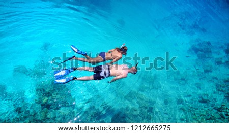 Top view of couple snorkeling in clear tropical waters with coral background #1212665275