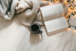Top view of cozy blanket, open book and hot cup of coffee on bed on a cold winter day. Relaxation and hygge concept. Top view with copy space