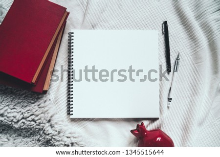 Top view of cozy workplace: open artbook, sketchbook, blank square page with pen and pencil. Hygge styled flat lay. Concept for art motivation, ready for sketching, drawing. Place for text, copy space