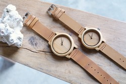 Top view of craft wooden couple watches and brown leather band on wood and white coral. Hand watch products for woman and man.