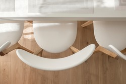 Top view of creamy white three chairs and white dining table with  beautifully filled sunshine in dining room