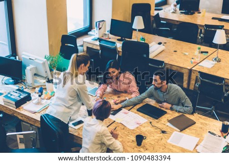 Top view of creative productive working process and discussion of skilled designers prepare project, male and female colleagues discussing ideas and drawing graphic together sitting a table  #1090483394