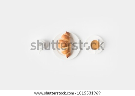 top view of cup of coffee and croissant for breakfast on white surface