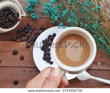Cup of coffee with hands on table in cafe background Images
