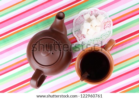 Top view of cup of tea and teapot on colorful tablecloths