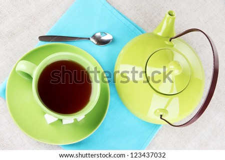 Top view of cup of tea and teapot on tablecloths